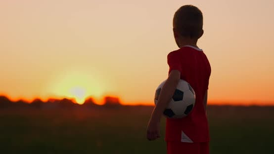 Thumbnail for A Boy with a Football Looks at the Sunrise