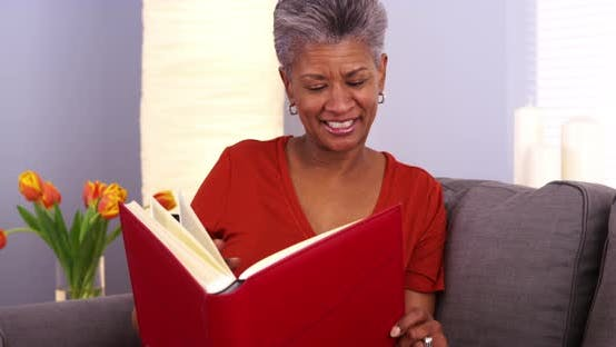 Thumbnail for Mature African woman looking through photo album