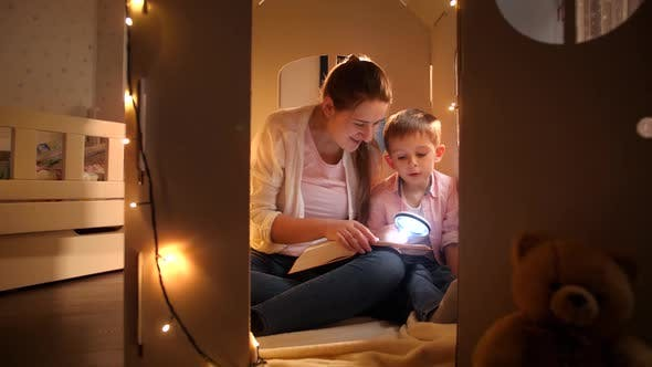 Happy Smiling Boy with Young Mother Sitting in Tent or Toy Cardboard House and Reading Book with