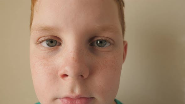 Portrait of Desperate Ginger Kid Looking Into Camera Inside. Little Serious Red-haired Boy with