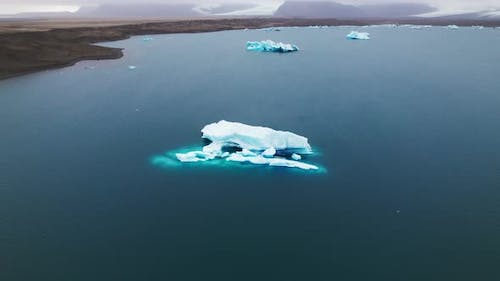 Iceberg Floating on Top Of the Blue Sea Against Clear Sky and Gray Clouds