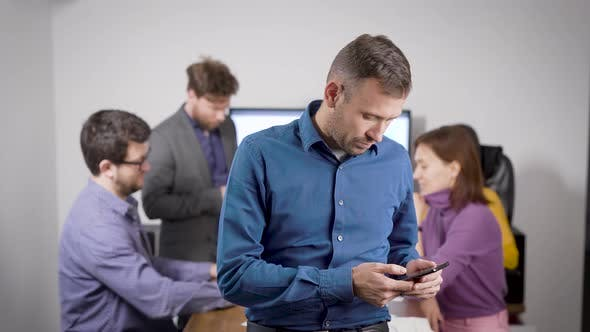Cover Image for Man Is Checking E-mail By Cell Phone in Office in Conference Hall and Answering on Message