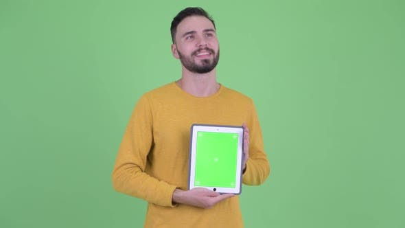 Thumbnail for Happy Young Handsome Bearded Man Thinking While Showing Digital Tablet