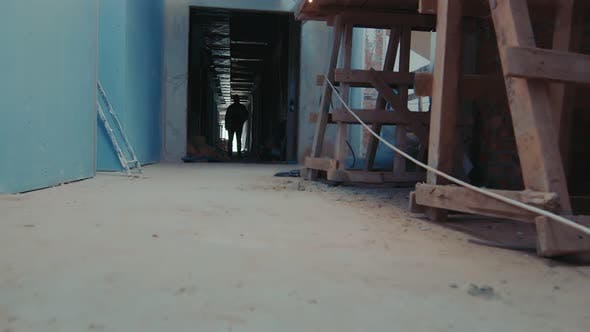 Cover Image for Welding Sparks Falling To the Ground. Silhouette of a Man in a Construction Corridor.