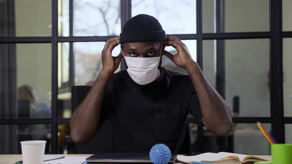 Darkskinned Male Putting on Face Mask on Camera