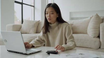 Asian Woman with Laptop and Calculator in the Living Room