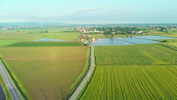 Thumbnail for Aerial: flying over rice paddies, flooded cultivated fields farmland rural italian countryside