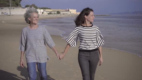Thumbnail for Smiling Women Walking on Sandy Beach
