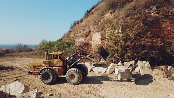 Thumbnail for Bulldozer is Working Near Sand Quarry on the Background of Stones