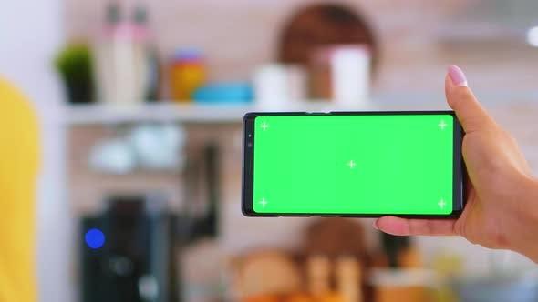 Thumbnail for Frau Hand hält Smartphone mit grünem Bildschirm