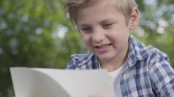 Cover Image for Close Up Portrait of Cute Handsome Boy in Checkered Shirt Looking at the Sheets of Paper in the Park
