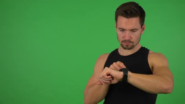 Thumbnail for A Young Handsome Athlete Works on a Touchscreen Wristwatch - Green Screen Studio