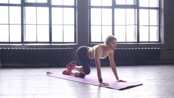 A Young Blonde Woman Is Doing Sports Doing Leg Exercises In A Fitness Studio With Large Windows