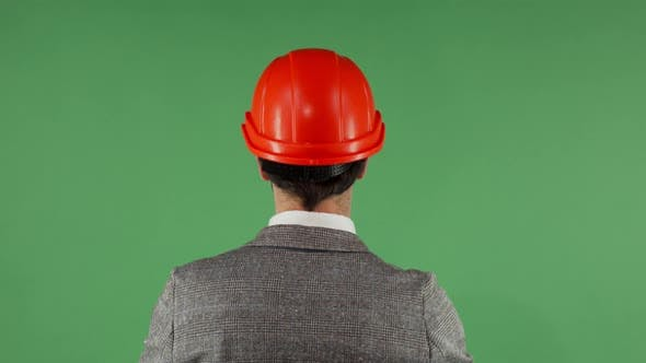 Thumbnail for Rear View Shot of a Businessman Putting on Protective Hardhat