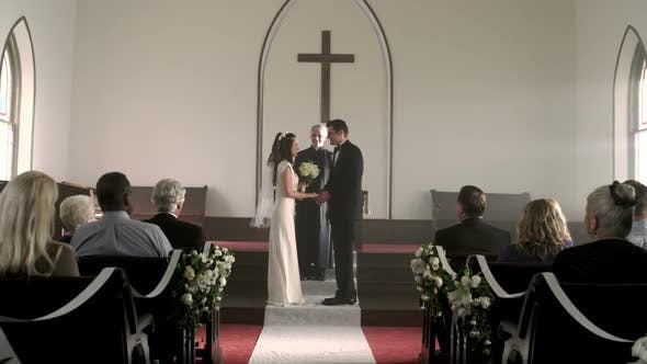 Newlywed couple kisses and walks down the aisle.