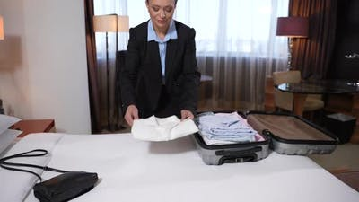 Businesswoman Unpacking Suitcase in Hotel Room