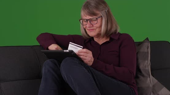 Happy elderly lady buying merchandise online with portable tablet on greenscreen