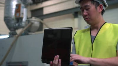 Industrial Engineer with Hard Hat Working with Laptop at Factory