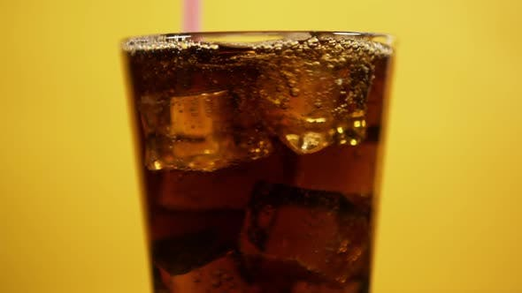 Thumbnail for Mixing Cold Cola Cocktail with Pink Drinking Straw. Glass Full of Fizzy Drink Ice Cubes on Yellow BG
