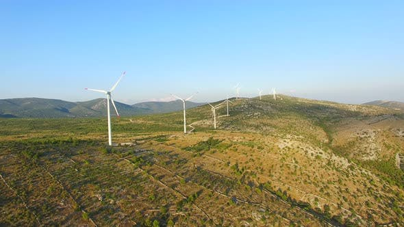 Flying above a group of white wind turbines with red tip blades on a sunny day