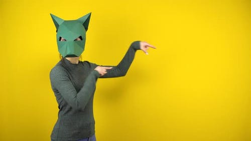 A Young Woman in a Cardboard Jackal Mask Points To the Empty Space with Her Index Fingers on a