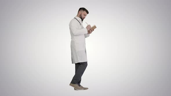 Thumbnail for Doctor or Medic Man Holding Pen and Notebook Looking for Idea While Walking on Gradient Background