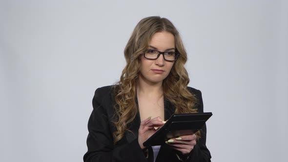 Woman Office Worker Makes Calculations on a Calculator Over Gray Background at Studio