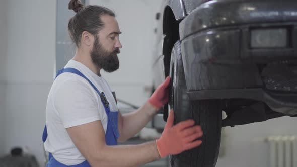 Thumbnail for Bearded Mechanic Inspecting Suspension or Brakes in Car Wheel of Lifted Automobile at Repair Service
