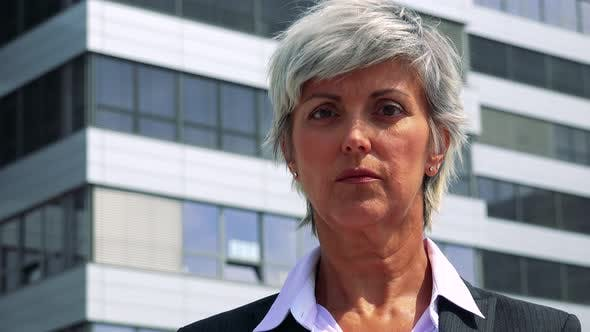 Thumbnail for Business Middle Age Woman Looks To Camera with Serious Face - Company Building