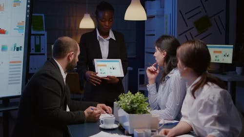 Focused Workaholic African American Businesswoman Showing Financial Graphs on Tablet
