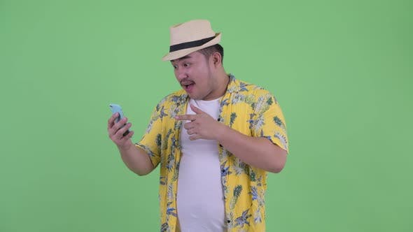 Cover Image for Happy Young Overweight Asian Tourist Man Video Calling and Showing Phone