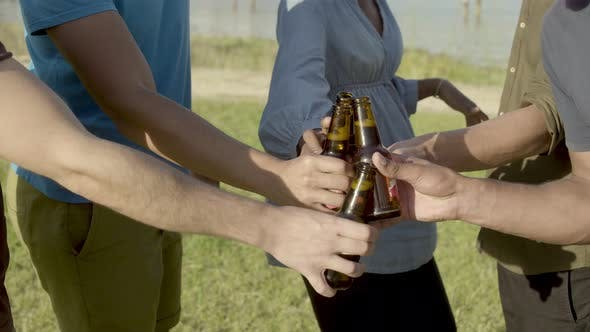 Thumbnail for Cropped Shot of Friends Clinking Beer Bottles and Dancing