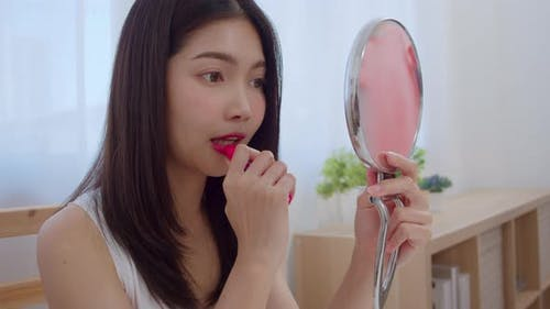 young Asian woman using lipstick make up in front mirror, Happy female using beauty cosmetics