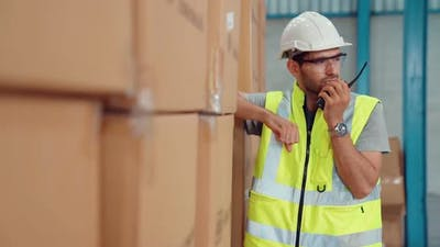 Professional Cargo Worker Talks on Portable Radio to Contact Another Worker