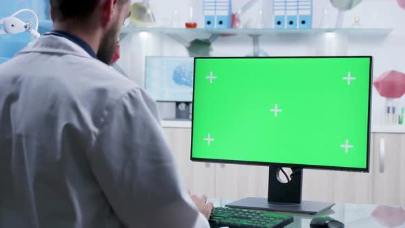 Thumbnail for Zoom in Shot on Doctor Typing on Green Screen Computer