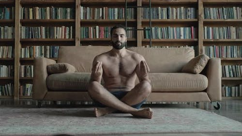 Guy With Naked Torso Meditates In The Library