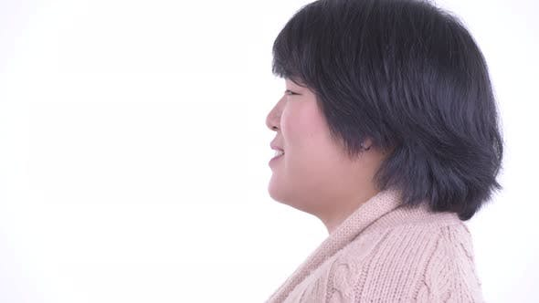 Thumbnail for Closeup Profile View of Happy Overweight Asian Woman Talking and Ready for Winter