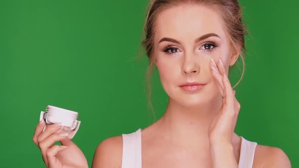 Thumbnail for Woman Applying Cream Under Her Eye and Laughing