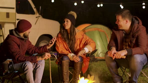 Thumbnail for Group of Close Friend Relaxing Together Around Camp Fire in a Cold Night of Autumn
