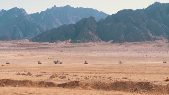 Thumbnail for Group on Quad Bike Rides Through the Desert in Egypt on Backdrop of Mountains. Driving ATVs.