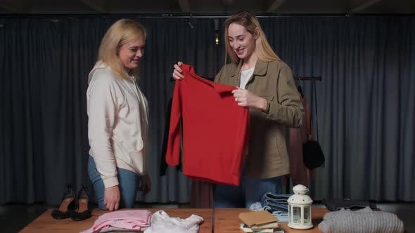 Young Women Second Hand Shop Workers Sort Clothes on Table