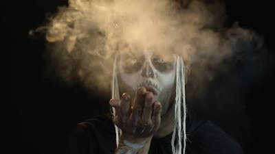 Sinister Man with Horrible Halloween Skeleton Makeup Making Fly Air Kiss with Smoke. Day of The Dead