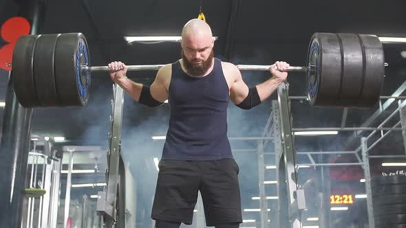 Starker aktiver Powerlifter, der versucht, schwere Langhantel-Reihe zu heben
