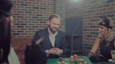 Man Interferes with a Deck of Cards and Looks at the Participants in the Game