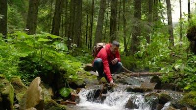 A Bearded Man with a Backpack Near a Mountain Stream