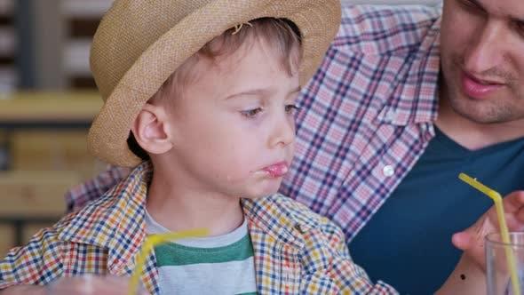 Thumbnail for Restaurant Essen, Little Boy genießt Fast Food und Saft sitzen am Tisch, während Sie mit den Eltern entspannen