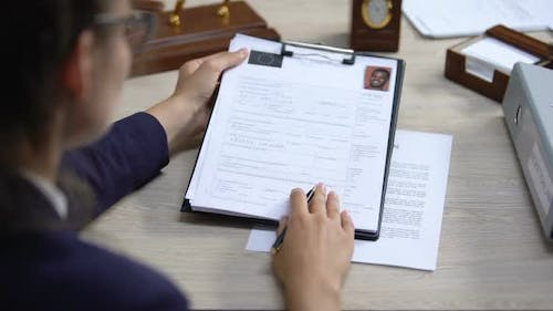 Employee Looking Through Visa Application and Signing Deportation Document