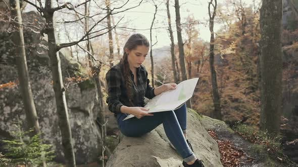 Woman Tourist Sitting on the Cliff in the Woods Looking at Tourist Map