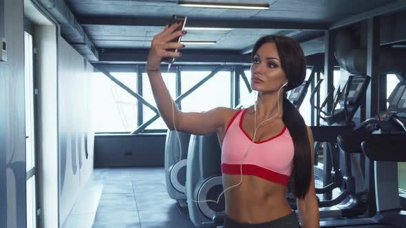 Thumbnail for The Sweet Girl Is Making Selfie on the Background of the Gym