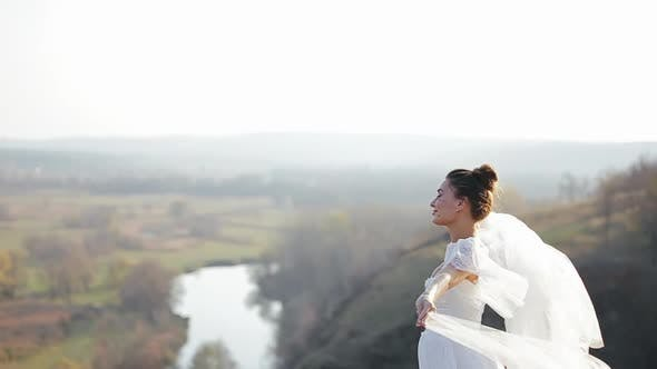 Thumbnail for Happy Pretty Bride in Chic White Wedding Dress Is Standing in Deserted Field on Windy Day and Waving